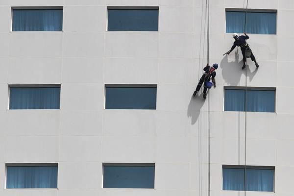 Pekerja membersihkan kaca gedung bertingkat di Makassar, Sulawesi Selatan, Selasa (16/1). - JIBI/Paulus Tandi Bone