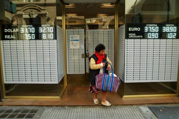 Seorang warga Argentina keluar dari kantor penukaran uang di Buenos Aires, Argentina, Rabu (29/8). - Reuters/Marcos Brindicci