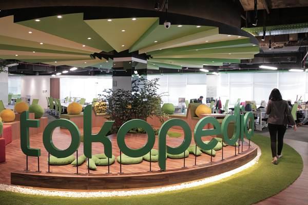 Ilustrasi: Seorang pegawai berjalan melewati logo Tokopedia - Tokopedia