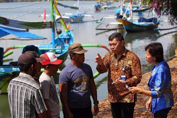 Direktur Teknologi XL Axiata Yessie D. Yosetya (dari kanan), dan Kepala Badan Riset & Observasi Laut I Nyoman Radiarta, memberi penjelasan kepada nelayan mengenai aplikasi Laut Nusantara, di Pantai Perancak Jembrana, Bali, Kamis (30/8/2018). - JIBI/Dwi Prasetya