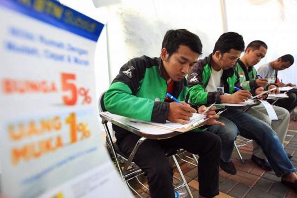 Pengemudi GO-JEK yang sudah mendapat pesan pendek berisi undangan pengajuan Kredit Pemilikan Rumah (KPR) BTN mengisi formulir pendaftaran di Kantor Pusat, PT Bank Tabungan Negara TBK (BTN) di Jakarta, Senin, (27/3). - JIBI/Dedi Gunawan