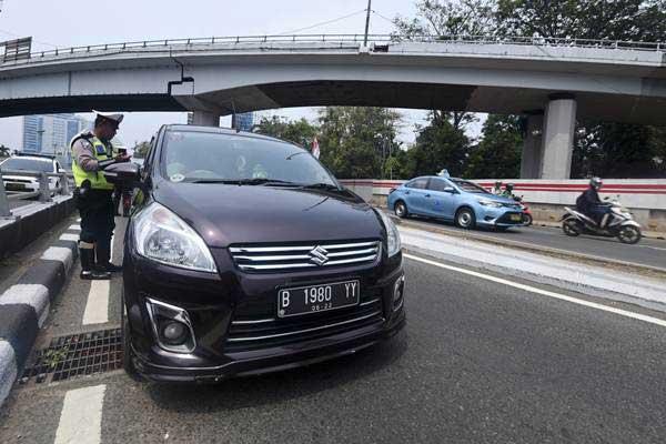 Petugas Ditlantas Polda Metro Jaya memberhentikan mobil berpelat nomor genap yang memasuki Jalan Gatot Soebroto, Jakarta, Rabu (1/8/2018). - Antara/Hafidz Mubarak