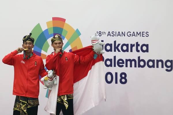 Pesilat Indonesia peraih medali emas Yola Primadona Jampil (kanan) dan Hendy (kiri) berpose usai penyerahan medali nomor ganda putra pencak silat seni Asian Games 2018 di Padepokan Pencak Silat Taman Mini Indonesia Indah (TMII), Jakarta, Senin (27/8/2018). - Antara/Tri Budi Prianto