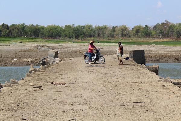 Warga memanfaatkan munculnya Jembatan Pondok untuk mencari ikan pada Rabu (12 - 9) pagi.