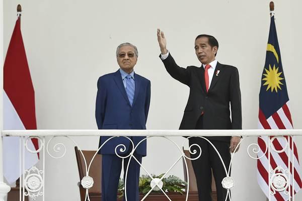 Presiden Joko Widodo (kanan) berbincang dengan Perdana Menteri Malaysia Mahathir Mohamad saat kunjungan kenegaraan di beranda Istana Bogor, Jawa Barat, Jumat (29/6/2018). - ANTARA/Puspa Perwitasari