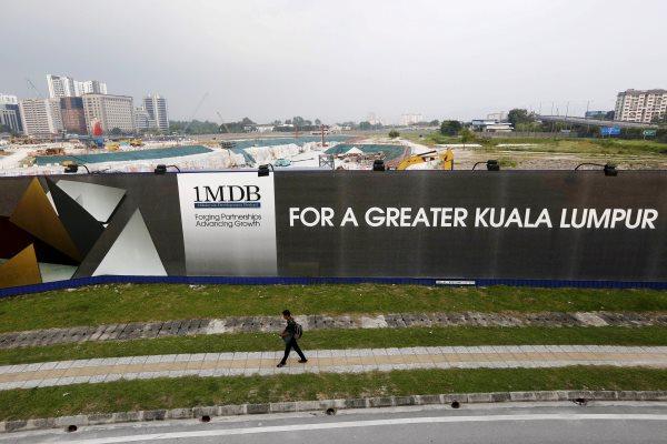 Seorang pejalan kali melintas di depan bilboard 1 Malaysia Development Berhad (1MDB) di  Kuala Lumpur (1/3/2015). - ReutersOlivia Harris