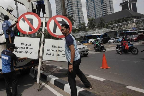 Petugas Dinas Pehubungan DKI Jakarta menurunkan rambu larangan kendaraan roda dua di sepanjang Jalan MH Thamrin, Jakarta, Rabu (10/1). - JIBI/Endang Muchtar