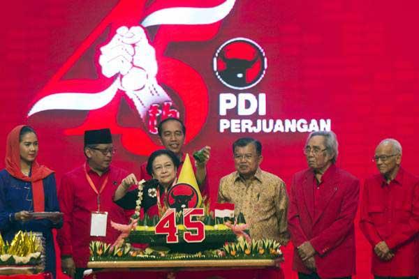 Ketua Umum PDIP Megawati Soekarnoputri (ketiga kiri) memotong tumpeng disaksikan Presiden Joko Widodo (keempat kiri), Wapres Jusuf Kalla (ketiga kanan), Sekjen PDIP Hasto Kristiyanto (kedua kiri) dan Deklarator Sabam Sirait (kedua kanan) dalam acara HUT ke-45 PDI Perjuangan di JCC, Jakarta, Rabu (10/1)./ANTARA FOTO - Rosa Panggabean