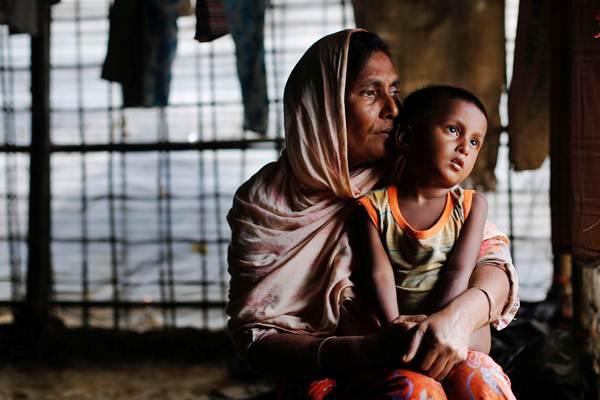 Perempuan pengungsi Rohingya bersama cucunya, saat menunggu bantuan, di Bangladesh, Selasa (19/9). - Reuters/Danish Siddiqui