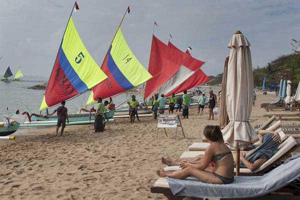 Wisatawan menyaksikan kompetisi perahu tradisional di Pantai Segara Ayu, Sanur, Bali. - ANTARA/Nyoman Budhiana