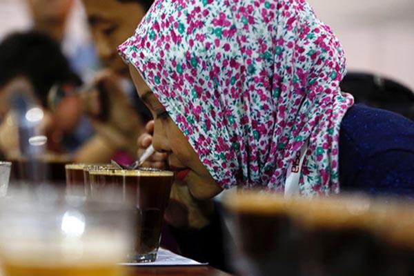 Seorang pengunjung menikmati minuman kopi dalam satu pameran kuliner di Jakarta - Reuters/Darren Whiteside