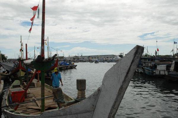 Seorang nelayan berjalan di antara perahu yang berlabuh di Dermaga - Bisnis/Lukman Gusmanto