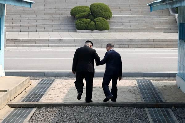 Pemimpin Korea Utara Kim Jong Un (kiri) bergandengan tangan dengan Presiden Korea Selatan Moon Jae-in saat pertemuan di desa gencatan senjata Panmunjom, Korea Selatan, Jumat (27/4/2018). - Reuters