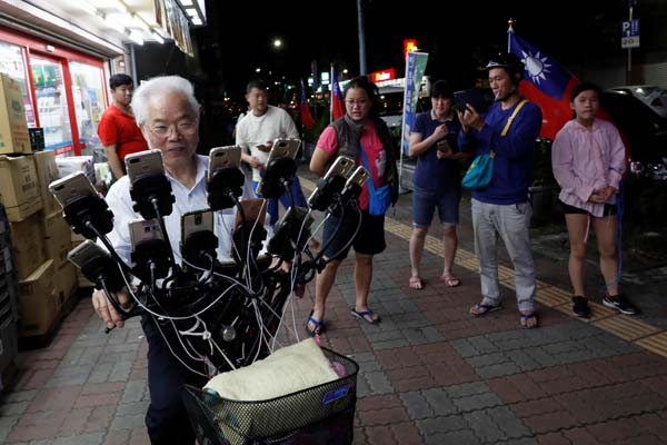 Kakek berusia 70 tahun bernama Chen San-yuan asyik bermain PokemonGo dengan 15 handphone di sepedanya menyisir di pinggiran Kota Taipei, ibukota Taiwan, Senin (12/11/2018). - Reuters/Tyrone Siu