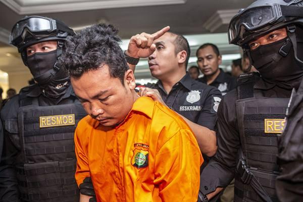 Petugas kepolisian melakukan pengamanan terhadap tersangka berinisial HS seusai rilis kasus pembunuhan satu keluarga, di Polda Metro Jaya, Jumat (16/11/2018). - Antara