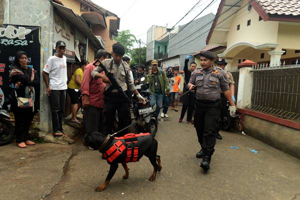Polisi melakukan penyisiran dengan anjing pelacak di sekitar lokasi perisitiwa pembunuhan satu keluarga, di kawasan Jatirahayu, Bekasi, Jawa Barat, Selasa (13/11/2018). Dalam peristiwa tersebut satu keluarga yang terdiri empat orang tewas dengan luka di tubuh. - Antara