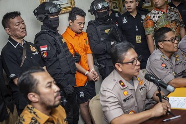 Petugas kepolisian melakukan pengamanan terhadap tersangka berinisial HS (tengah belakang) dalam rilis kasus pembunuhan satu keluarga yang disampaikan oleh Wakapolda Metro Jaya Brigjen Pol Wahyu Hadiningrat (tengah depan), di Polda Metro Jaya, Jumat (16/11/2018). - Antara