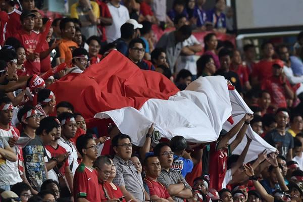 Suporter Indonesia membawa bendera merah putih ketika menyaksikan Timnas Indonesia melawan Filipina dalam pertandingan putaran I Sepak Bola SEA Games ke-28, di Stadion Jalan Besar, Singapura, Selasa (9/6). - Antara