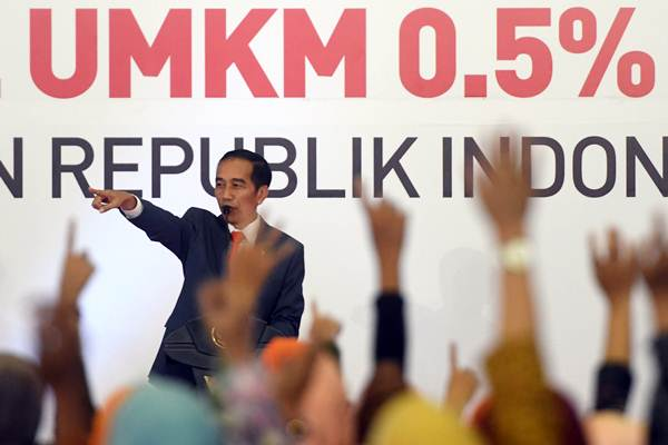 Presiden Joko WIdodo mengajukan pertanyaan kepada warga di sela peluncuran aturan penurunan tarif Pajak Penghasilan Final 0,5 persen bagi UMKM di Surabaya, Jawa Timur, Jumat (22/6/2018). - ANTARA/Zabur Karuru