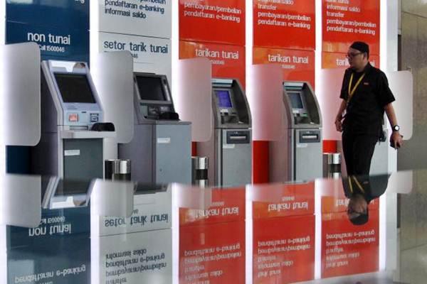 Nasabah melintas di dekat mesin ATM Bank BNI di Jakarta, Selasa (12/9). - JIBI/Abdullah Azzam