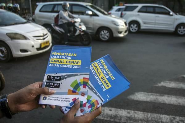 Petugas Badan Pengelola Transportasi Jabodetabek (BPTJ) melakukan sosialisasi kepada pengguna kendaraan bermotor pada hari pertama uji coba perluasan kawasan ganjil genap di persimpangan Pancoran, Jakarta, Senin (2/7/2018). - ANTAR/Aprillio Akbar