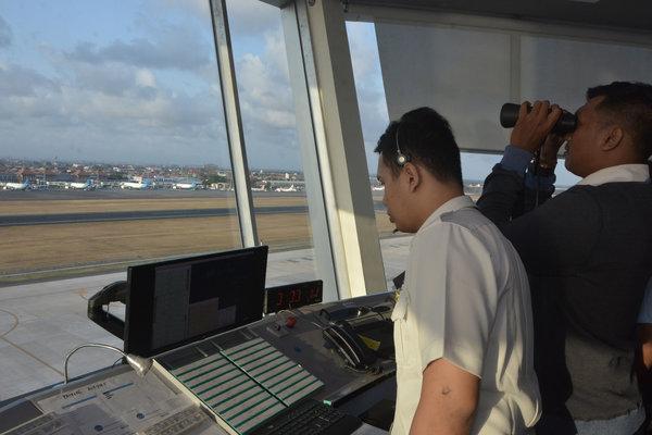 Petugas memantau dan mengatur pergerakan pesawat udara di menara Air Traffic Controller (ATC) Bandara Internasional I Gusti Ngurah Rai, Bali, Senin (8/10). - Antara/Fikri Yusuf