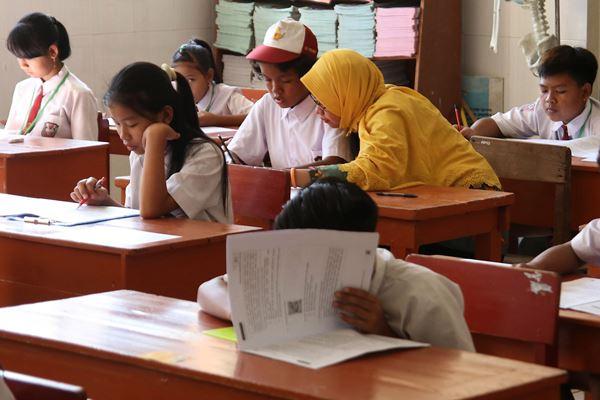 Ilustrasi - Guru pedamping membacakan soal Ujian Sekolah Berstandar Nasional (USBN) kepada murid berkebutuhan khusus di SD Inklusi Betet I, Kota Kediri, Jawa Timur, Kamis (3/5). - Antara