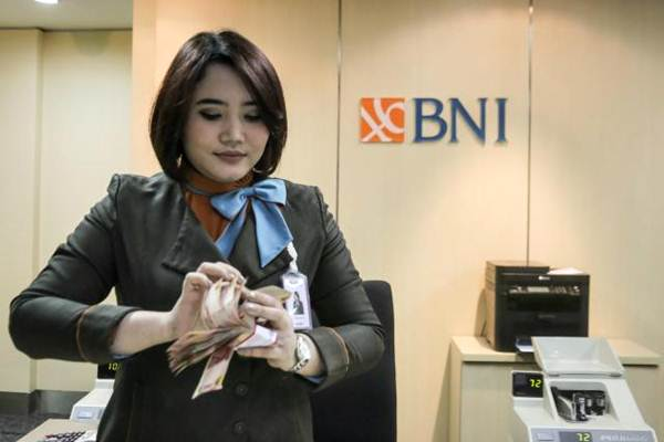 Karyawati Bank BNI menghitung uang Rupiah, di Jakarta, Senin (3/4/2018). - JIBI/Felix Jody Kinarwan