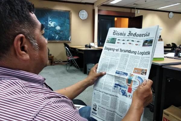 Pelanggan Bisnis Indonesia tengah membaca koran edisi hari ini, Jumat (23 - 11).