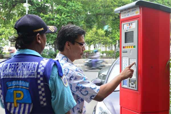 Pemilik kendaraan menggunakan mesin parkir ditemani Juru Parkir di kawasan Juanda, Jakarta, Senin (8/5). - Antara/Ariyanto