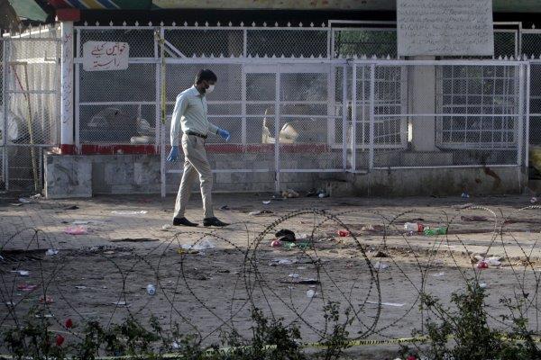 Petugas forensik sedang memeriksa lokasi bekas ledakan bom bunuh diri di Lahore, Pakistan. - Reuters/Mohsin Raza