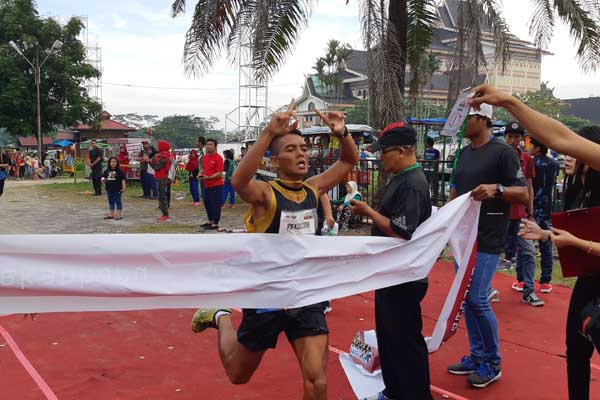 Peserta terbaik pertama peraih medali emas memasuki garis finish dalam event lari 10K Telkomsel LOOP Run di Pekanbaru, Minggu (25/11/2018). Telkomsel menggelar kegiatan LOOP Run yang diikuti ribuan peserta tahun ini dengan mengangkat tema Mobile Legend, sebagai wadah gaya hidup sehat dan diminati generasi muda. - Bisnis/Arif gunawan