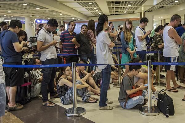 Wisatawan mancanegara menunggu keberangkatan pesawat di bandara Internasional Ngurah Rai, Bali - Bloomberg/Putu Sayoga