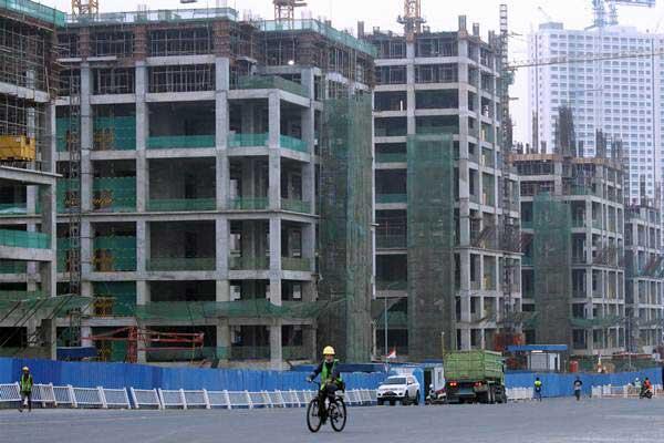 Pekerja beraktivitas di kawasan proyek pembangunan Apartemen - ANTARA/Risky Andrianto