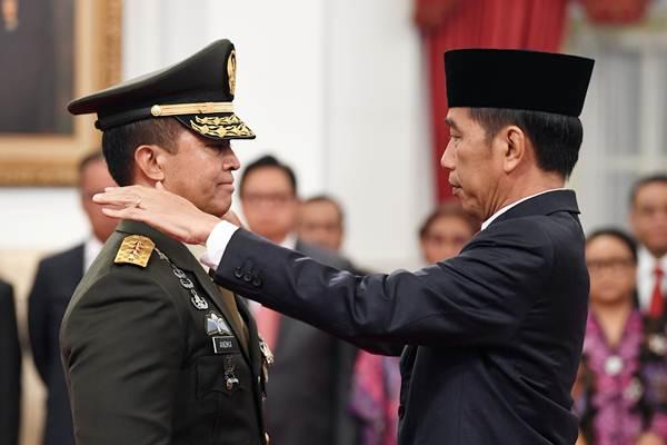 Presiden Joko Widodo (kanan) memasangkan tanda pangkat jabatan kepundak Kepala Staf Angkatan Darat (KSAD) yang baru Jenderal TNI Andika Perkasa (kiri) seusai pelantikan di Istana Merdeka, Jakarta, Kamis (22/11/2018). - ANTARA/Wahyu Putro A
