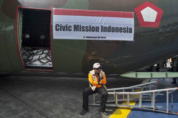 Relawan duduk di depan pesawat Hercules yang akan diberangkatkan untuk mengirim bantuan kemanusiaan Rohingya di Base Ops TNI AU Halim Perdanakusuma, Jakarta, Rabu (13/9). - ANTARA/Rosa Panggabean