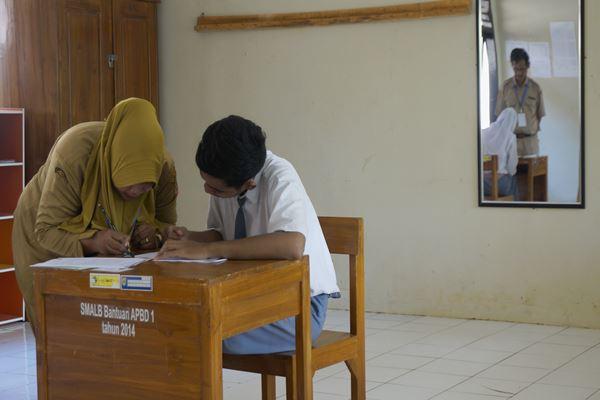 Pengawas mendampingi siswa tuna rungu dengan bahasa isyarat saat mengikuti Ujian Nasional Berbasis Kertas dan Pensil (UNBKP) di Sekolah Luar Biasa (SLB), Kabupaten Batang, Jawa Tengah, Senin (8/4). - Antara