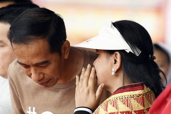 Calon Presiden nomor urut 01 Joko Widodo (kiri) mendapat bisikan dari Ibu Negara Iriana Joko Widodo saat menghadiri jalan sehat bertajuk Sehat Bersama 01JokowiLagi di Lampung, Sabtu (24/11/2018). - ANTARA/Puspa Perwitasari