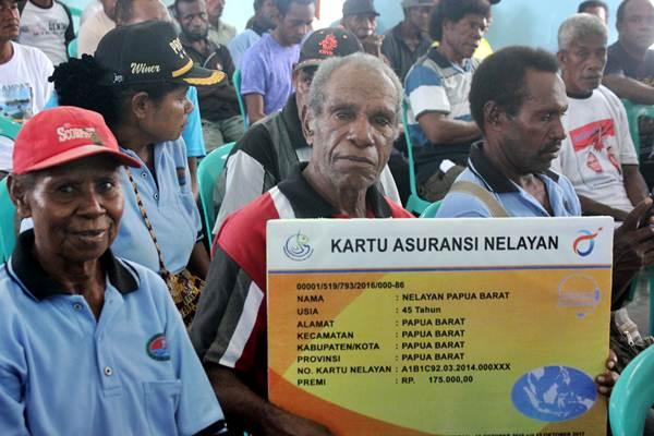 Nelayan memerlihatkan replika kartu Asuransi Nelayan di Kota Sorong Papua Barat, Selasa (21/2). - Antara/Olha Mulalinda