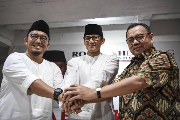 Sandiaga Uno (tengah) berjabat tangan dengan Ketua Umum PP Pemuda Muhammadiyah Dahnil Anzar Simanjuntak (kiri) dan mantan Menteri ESDM Sudirman Said (kanan) saat deklarasi dukungan pasangan capres-cawapres Prabowo Subianto-Sandiaga Uno di Roemah Djoeang, Jakarta, Jumat (21/9). Dahnil Anzar Simanjuntak yang ditunjuk sebagai Koordinator Juru Bicara Badan Pemenangan Nasional mendeklarasikan dukungan terhadap pasangan Prabowo Subianto-Sandiaga Uno pada Pemilihan Presiden 2019.  - Antara