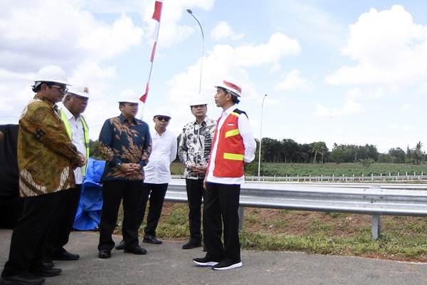 Presiden Joko Widodo (kanan) didampingi Menteri PUPR Basuki Hadimuljono (kedua kiri), Seskab Pramono Anung (kiri), Gubernur Lampung Ridho Ficardo (ketiga kiri), Koordinator Staf Khusus Presiden Teten Masduki (ketiga kanan) dan Anggota DPR Aziz Syamsuddin (kedua kanan) meninjau pembangunan jalan tol Bakauheni-Palembang, di Lampung, Jumat (23/11/2018). - ANTARA/Puspa Perwitasari