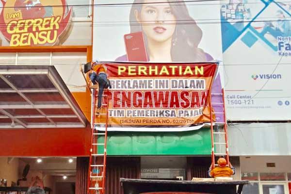 : Papan reklame di Kota Malang dipasangi stiker karena belum dibayar pajaknya - Istimewa