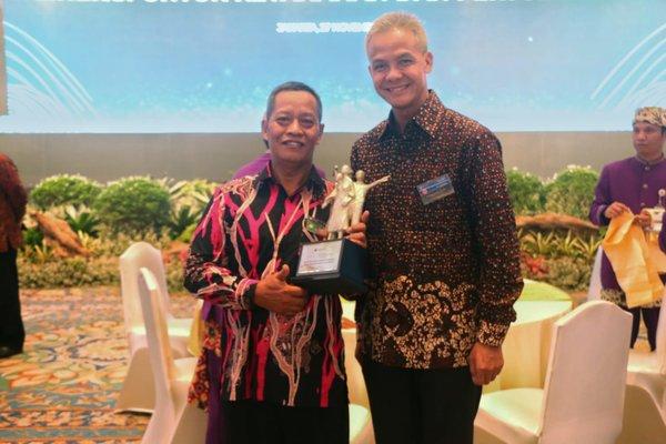 Gubernur Ganjar Pranowo berfoto bersama Mustofa dari Gapoktan Al Barokah penerima Bank Indonesia Award 2018 Klaster terbaik pendukung ketahanan pangan kategori pengendalian inflasi, sub sektor klaster tanaman pangan.