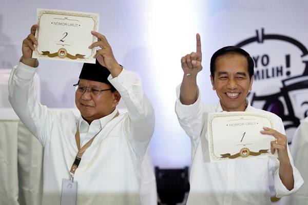 Calon Presiden dalam Pilpres 2019 Joko Widodo (kanan) dan Capres Prabowo Subianto memperlihatkan nomor urut masing-masing, di kantor KPU, Jakarta, Jumat (21/9/2018). - Reuters/Darren Whiteside