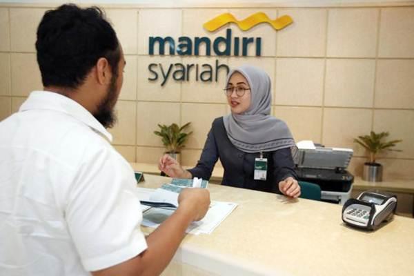 Karyawan melayani nasabah di kantor cabang Bank Syariah Mandiri di Jakarta, Senin (8/12). - JIBI/Abdullah Azzam