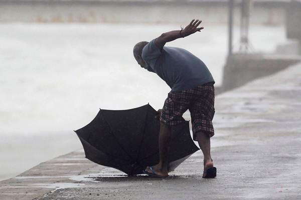 Seorang pria berusaha mengejar payungnya yang jatuh saat hujan di Kolombo, Sri Lanka, Jumat (01/12). - Reuters/Dinuka Liyanawatte