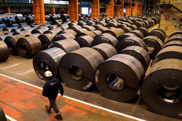 Seorang pekerja berjalan melewati gulungan baja di pabrik baja ArcelorMittal di Sestao, Spanyol, 12 November 2018. Reuters  - Vincent West