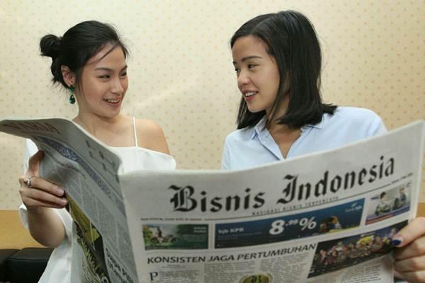Vice President Strategy & Business Development PT Digital Indonesia Raya Nicole Yap (kanan) bersama Head of Startup Relations Alyssa Maharani membaca koran saat berkunjung ke kantor redaksi Bisnis Indonesia, di Jakarta, Selasa (8/5/2018). - JIBI/Dedi Gunawan