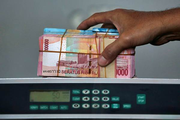 Karyawan menghitung uang rupiah. - Reuters/Willy Kurniawan