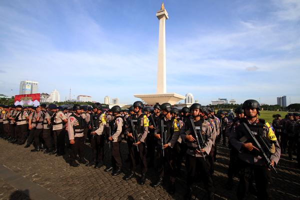 Anggota kepolisian mengikuti Apel Gelar Pasukan Operasi Lilin 2016 di Monas, Jakarta, Kamis (22/12). Kepolisian Republik Indonesia memastikan situasi selama Natal dan Tahun Baru 2017 aman dari ancaman. - Antara